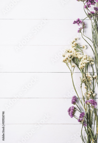 Naklejka Bouquet of dried wild flowers on a white background of vintage wooden planks top view vertical