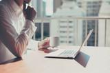 コーヒーを飲みながら窓際でノートパソコンを使っているビジネスマン - 101955301