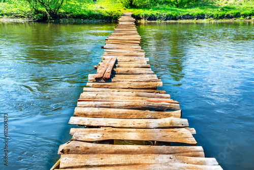 Old wooden bridge through the river Poster