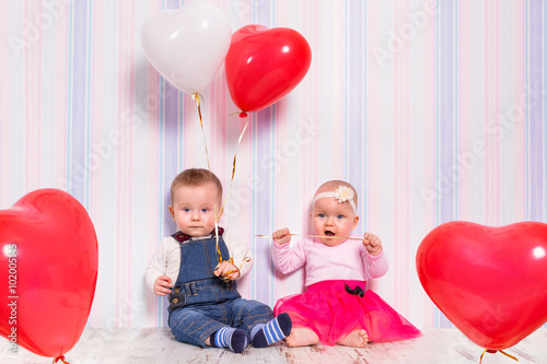 Poster Baby boy and girl playing with heart balloons for valentines day