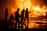 Silhouette of Firemen fighting a raging fire with huge flames of burning timber - 102013931