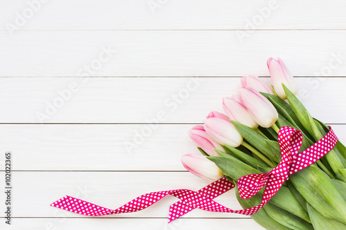 Bouquet of pink tulips on white wooden background. Top view