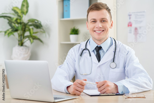 Smiling pediatrician sitting at the table Poster