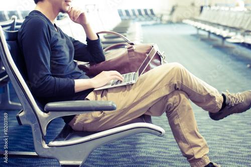 空港の待合室でノートパソコンを使っている男性 Poster