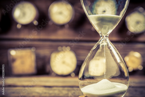 Fototapeta Aged hourglass with flowing sand