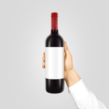 Blank white label mockup on black bottle of red wine in hand isolated.