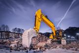 Fototapety huge orange shovel digger on demolition site at night