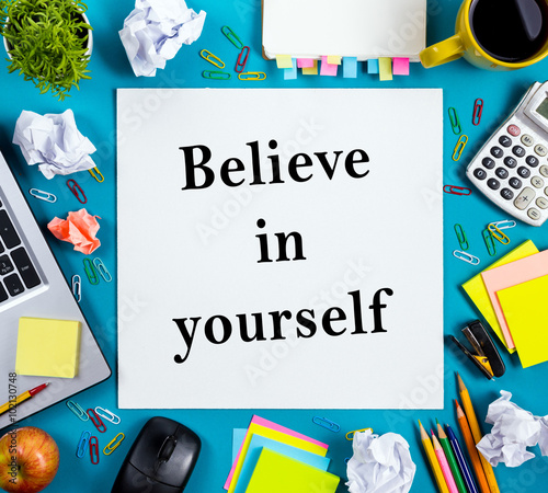 Believe in yourself. Office table desk with supplies, white blank note pad, cup, pen, pc, crumpled paper, flower on wooden background. Top view Photo by projectio