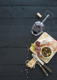 Wine appetizer set. Glass of red wine, French sausage and olives on black wooden backdrop - Fine Art prints