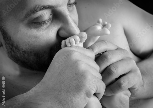 Father kisses the feet of a young child.