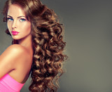 Fototapety Beautiful model brunette with long curled hair . Hairstyle wavy curls . .Makeup color fuchsia .