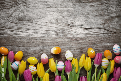 Tulips and easter eggs on wood background