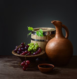 bowl with red wine pitcher with a barrel and grapes