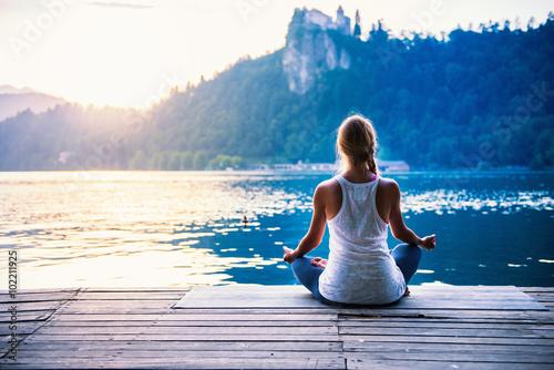 Obraz na płótnie Joga lotosu. Młoda kobieta robi joga nad jeziorem, siedząc w pozycji lotosu.