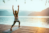 Fototapety Yoga Sun Salutation. Young woman doing yoga by the lake at sunset, saluting to the sun.