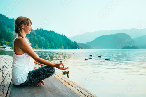 Poster Meditation. Young woman meditating by the lake.