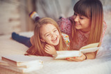 Portrait of a smiling young cute mother and daughter reading a book lying and relax in the bed in a bright big white room  - Fine Art prints