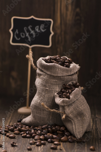 Fotobehang Koffiebonen Coffee beans in burlap bags over wooden background. Vintage style. Toned image. Selective focus