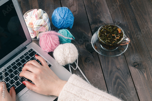 Poster woman is knitting in front of laptop