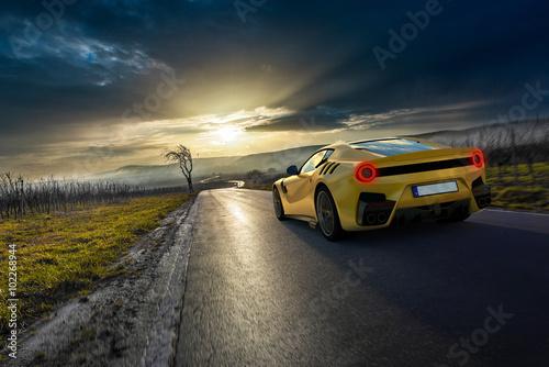 obraz PCV gelber Supersportwagen auf Pfälzer Landstraße vor Sonnenuntergang