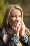 junge blonde Frau niest ins Taschentuch