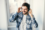 Happy young man listens to music in headphones