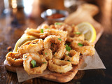 crispy calamari rings on woodne tray with lemon wedge - 102319111
