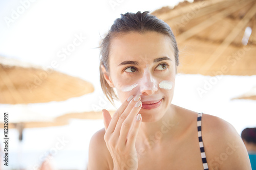beautiful woman smears face sunscreen at the beach for protection © timonko