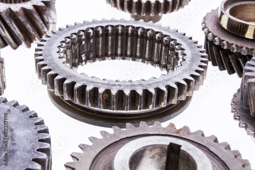 Large group of rusty transmission gears on a white background. Poster