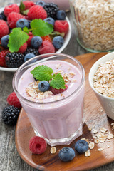 berry smoothie with oatmeal in a glass on wooden table, vertical