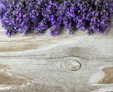 Fresh lavender flowers on a wooden background. Decorative border or frame with lavander and old wooden plank. Photo above.