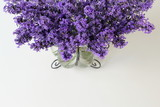 Bouquet of lavender flowers in a vase on a white background. Photo from above.
