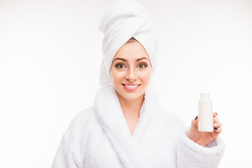 Pretty girl with towel on her head holding lotion © deagreez