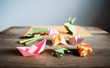Origami figures, scissors and pencils on wooden table.