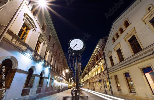 Zdjęcia na płótnie, fototapety na wymiar, obrazy na ścianę : Antique clock on Piotrkowska Street, Lodz, in the evening.