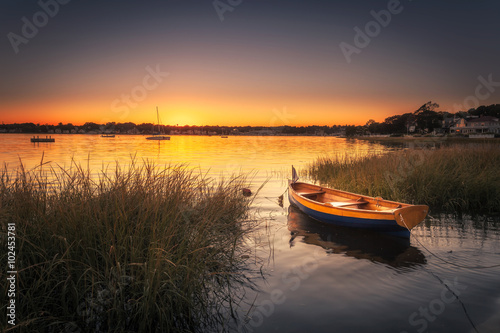 Small Boat in Harbor at Sunset - 102453781