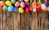 Easter eggs and tulips on wooden background