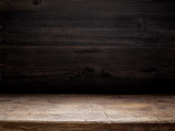 Fototapety wooden table and dark wooden wall