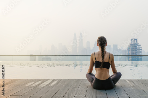 Relaxed young yoga woman in yoga pose near pool. плакат