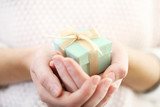Fototapety Female hands holding beautiful small gift wrapped with satin ribbon.
