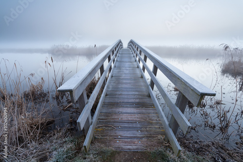 obraz PCV wooden bridge via river in winter