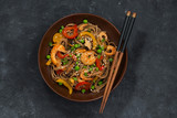 Buckwheat noodles with seafood in a bowl, top view