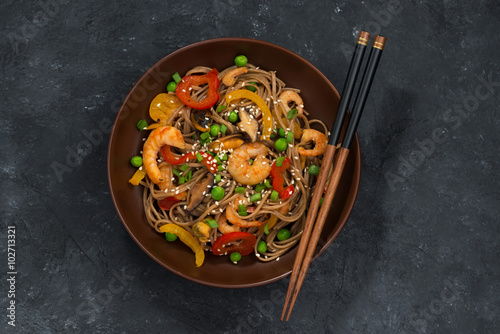 Juliste Buckwheat noodles with seafood in a bowl, top view