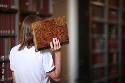 Poster Academic session; rear view of a man with an old book in hand
