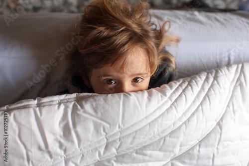 Bambina gioca a letto sotto il piumone Poster