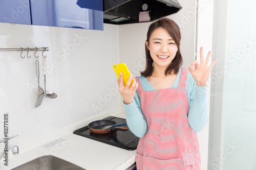 キッチンでスマホを見る女性
