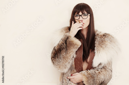 Poster A woman in a fur coat smoking cigarette.