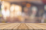 Fototapety Wooden board empty table in front of blurred background. Perspective brown wood over blur in restaurant - can be used for display or montage your products.Mock up for display of product.