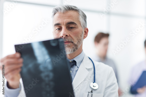 Radiologist examining a patient's x-ray Plakat