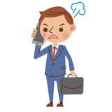 スマートフォンで通話する若いビジネスマン(怒った表情)